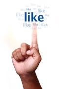 Foto, das Facebook symbolisieren soll. Foto, bei dem ein Finger auf den Begriff like zeigt.